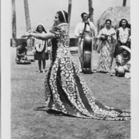 Woman in holoku performing hula
