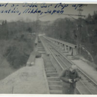 An American soldier holding a camera on railroad at…