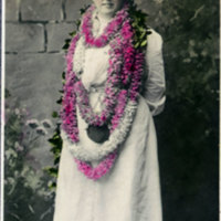 Woman in long dress with lei and hat - colorized…