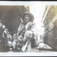 Woman Wearing Leis and a Man Standing by a Ship