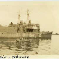 A Japanese ship and several people in a small boat at…