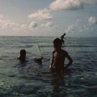 Young Boys and Model Canoe in Ocean