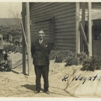 R. Nagata in a suit standing with a jeep in the…