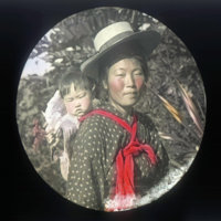 Japanese woman wearing a straw hat with child on back