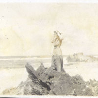 Woman Standing on Rocks at a Beach