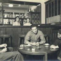 Three Amerians playing cards at the table and two…
