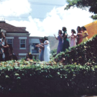 [Parade float with dancers and musicians]
