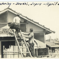 Two Japanese men plastering a wall in a Japanese house,…