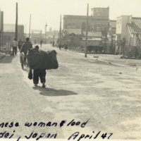 A Japanese woman carrying a huge load on her back on a…