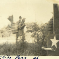 A soldier with a woman carrying a basket on her back,…