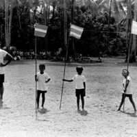 Young boys stand by flags, waiting to begin a race at…