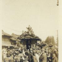 A festival float (Dashi 山車) with many spectators near…