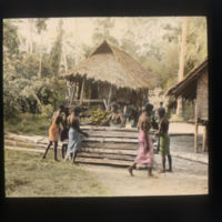 Thatched houses and villagers working with wooden slats