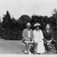 2 Men and 1 Woman Sitting On a Garden Bench