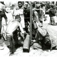 Marines give water to civilian prisoners, (men).