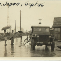Japanese men and children standing near American jeep…