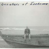 Emery Middleton sitting on a wooden boat on seashore of…