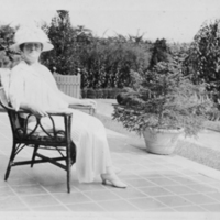 Woman Sitting In Chair On Outdoor Terrace
