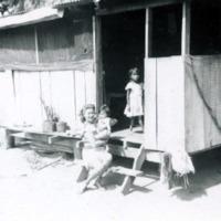 Rosalie Maxey outside native house. Guam. Fish net.…