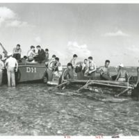 Natives assist Marines by loading five-gallon water…