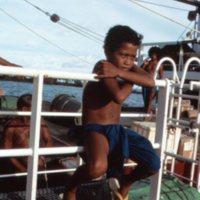Boy Sitting on Ship Railing