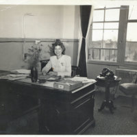 Aileen Kerrigan at her office desk with two telephones…