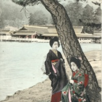 [Two girls in kimono standing and sitting next to a…