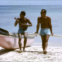Two men sitting on a canoe on a beach