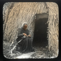 Woman in black muumuu sitting outside thatched building…