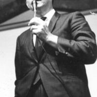 Speaker [Asian man, standing, holding microphone]