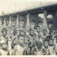 Kaizawa 2-103: Many Japanese children near a riverbank,…