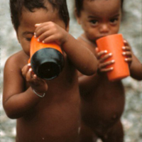 Two Young Children with Orange Cups