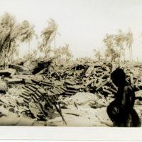 A soldier standing near an artillery gun and empty…