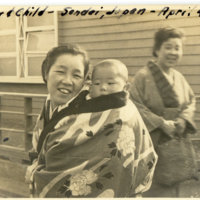 A Japanese woman carrying a baby on her back while…