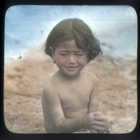 Young child sitting on sand