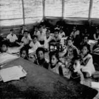 Lelu school third graders seated on mats, 1962?…
