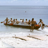Tourists in a canoe at a beach