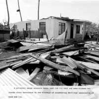 Concrete home missing roof, amidst debris of wooden…