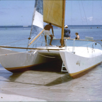People in a sailboat at a beach