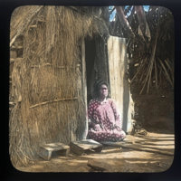 Hawaiian woman sitting in doorway of thatched building