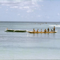 People canoeing and surfing at a beach