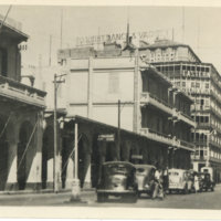 Street scene with some cars and people. A building…