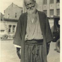 An elderly man with a long grey beard dressed in kimono…