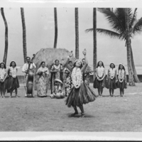Woman performing hula with dancers and musicians…