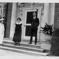 2 Women and 1 Man Standing On Steps In Front Of Doorway