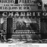 [Mexican storefront, sign reading: Exquicitos Pulques…