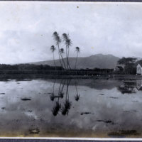 Marsh or pond, farm building with mountains in…