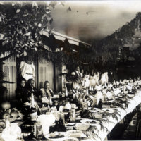 Banquet table with seated and standing Hawaiians