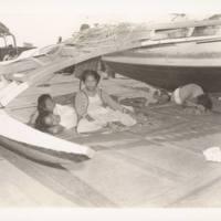 Rongelap ladies relax beneath outrigger canoe
