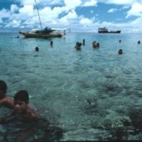 People Swimming in Reef; Ship and Canoe in Background
